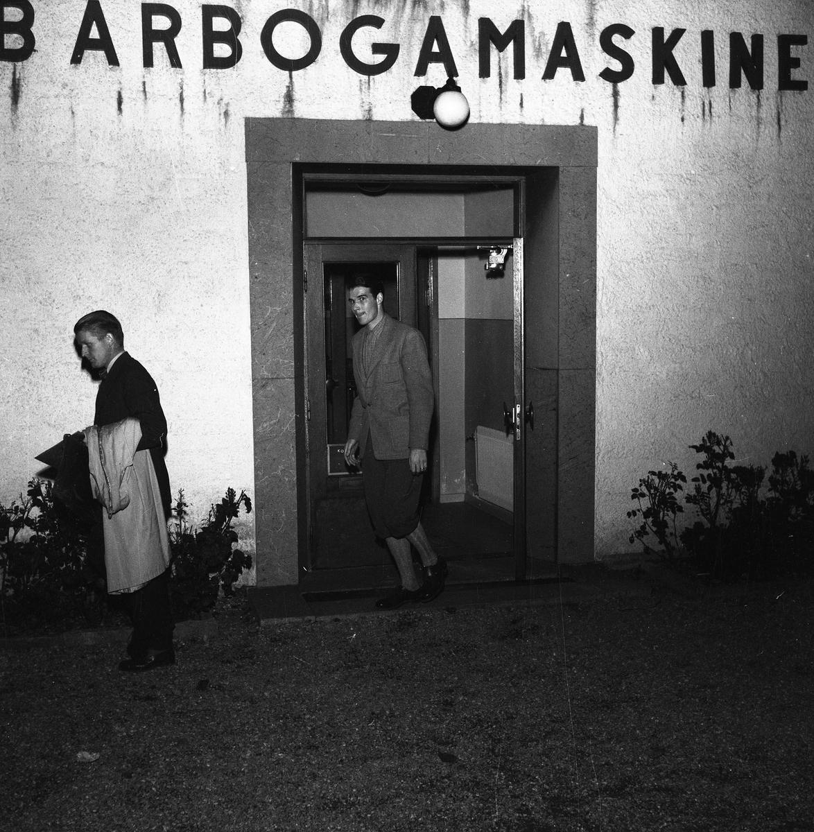 Arboga Maskiner, entré. En kostymklädd man, med överrocken på armen och en mörkhårig man iklädd kavaj och knäbyxor går ut från AB Arboga Maskiner. Mannen i knäbyxor är Göte Wahlfeldt. Han är arbetsstudieingenjör.