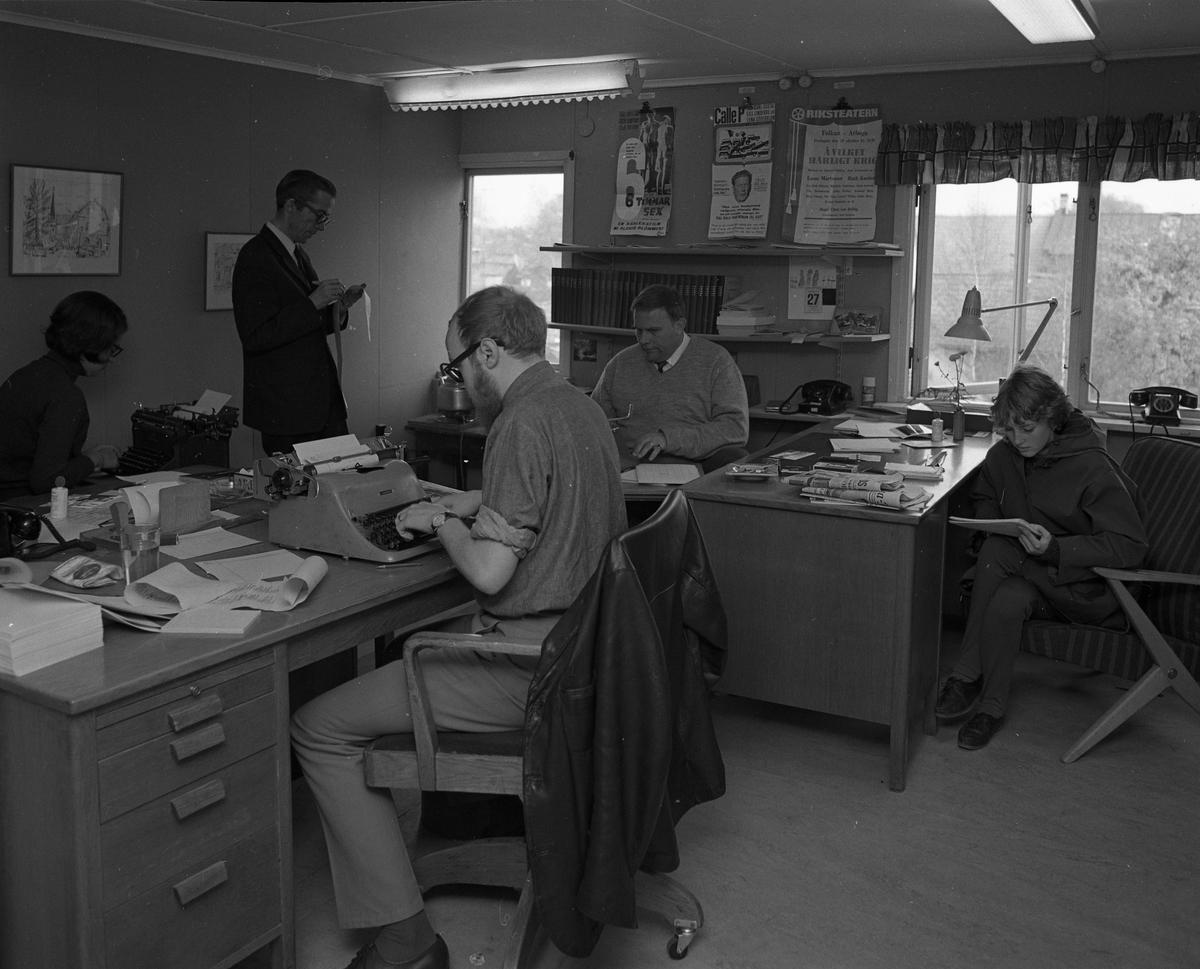 Arboga Tidning, personal och interiör. Fem personer på kontoret. Tre journalister arbetar vid sina skrivmaskiner. En person sitter vid skrivbordet och läser anteckningar. En man står upp och har ett långt papper i handen. På skrivborden syns telefoner, askfat och tidningar. På väggen, mellan fönstren, hänger bio- och teater affischer.