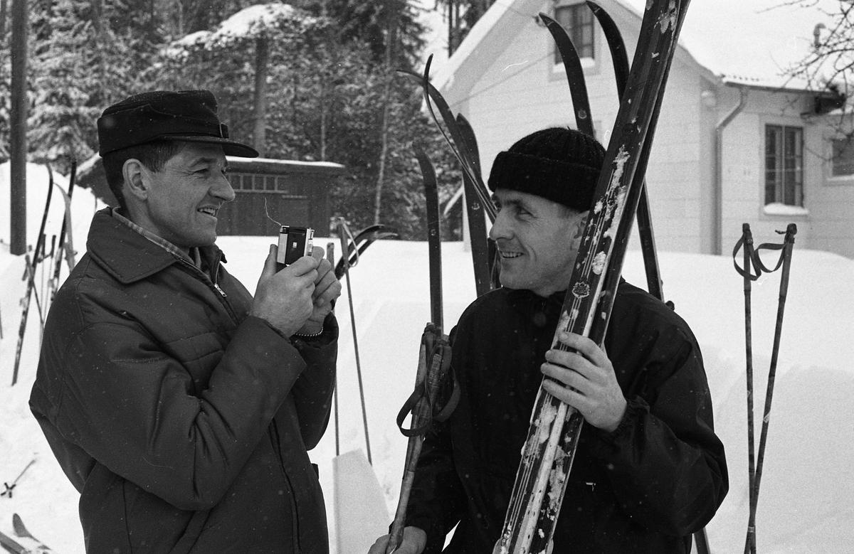 Skidtävlingen AT-loppet. Till vänster, med kameran, Lennart Pettersson (kallad Svarten), till höger, med skidorna, Torsten Eriksson. Båda männen bor i Medåker. (AT kan betyda Arboga Tidning) I bakgrunden ses ett hus.