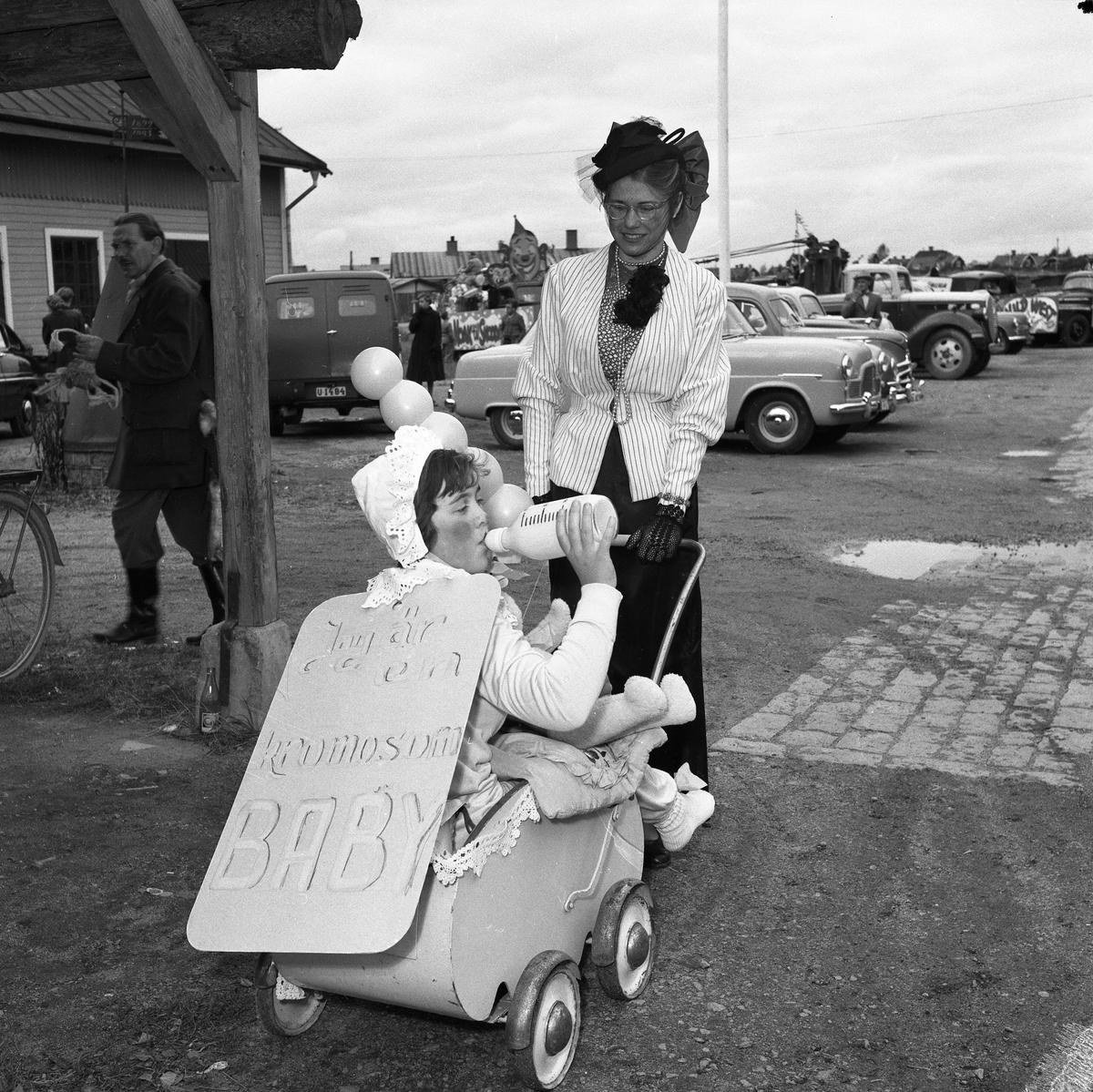 Barnens Dag firas. Här en mamma med en ovantligt stor baby i vagnen. Bakom dem skymtar diverse personbilar på parkeringen.