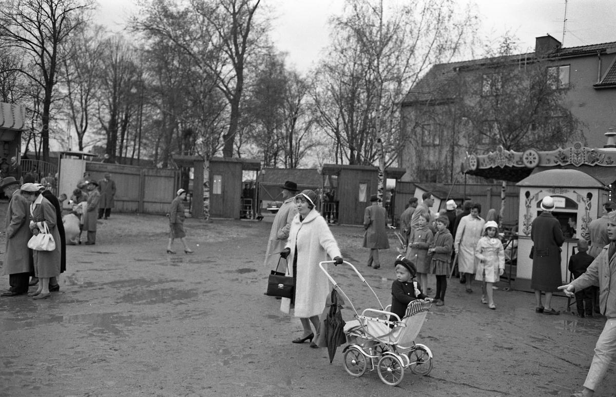 Barnens Dag firas på Sturevallen med karuseller och lottstånd. Människor i alla åldrar har kommit till festplatsen trots att det har regnat. I förgrunden ses en kvinna med ett barn i vagn. Hon har paraply med sig. I bakgrunden ses träden i Olof Ahllöfs park.