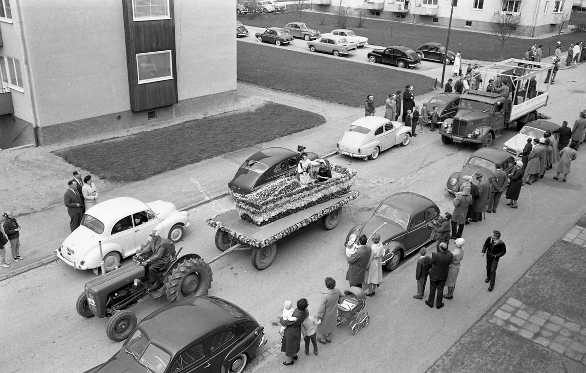 Barnens Dag firas med en kortege genom staden. Närmast i bilen är en traktor med vagn, dekorerad med blommor. Bilar står parkerade längs Österled och publiken står på trottoaren.