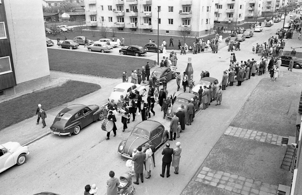Barnens Dag firas med en kortege genom staden. Här kommer de sista grupperna; en musikgrupp i svarta kläder och långa skägg och, som sig bör Arboga öl. Bilar är parkerade längs gatan och publiken står på trottoaren. Flerbostadshusen i bakgrunden ligger i kvarteret Långa Raden.