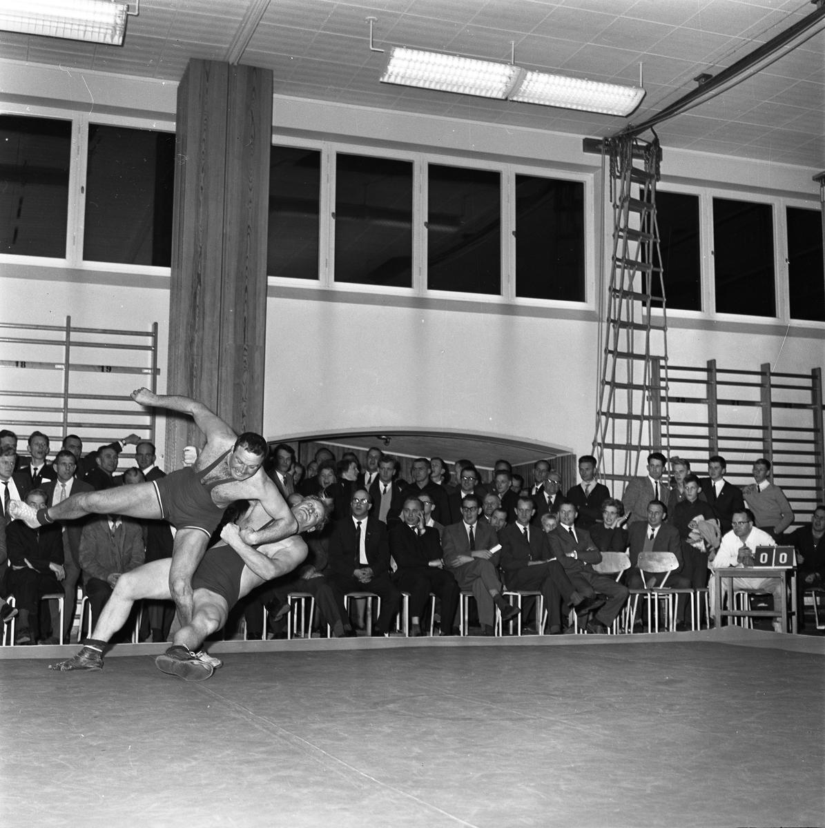 Tävlingen Fyrstadsbrottning mellan Arboga Atletklubb, Eslöv, Uddevalla och Falkenberg. Två män ovanför brottarmattan. Publik i gymnastiksalen.