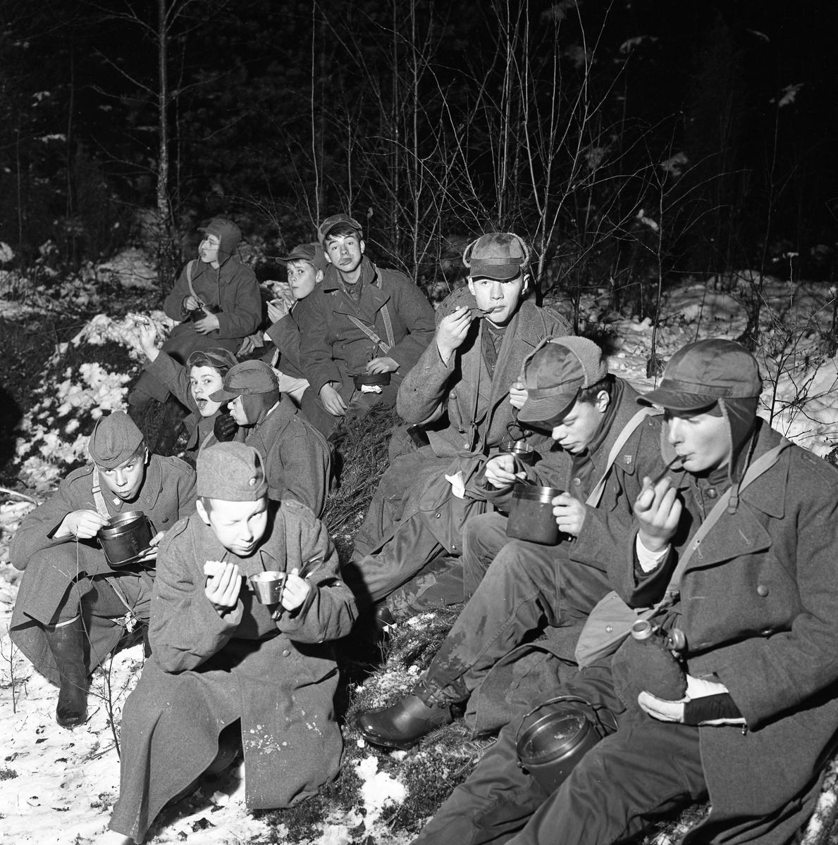 FBU-ungdomar övar i skogen. Det är vinter och snö. Grabbarna sitter på granris och äter ur sina plåtburkar. De är iklädda yllerockar och mössor med öronlappar. Några har båtmössor. FBU betyder Frivillig befälsutbildning