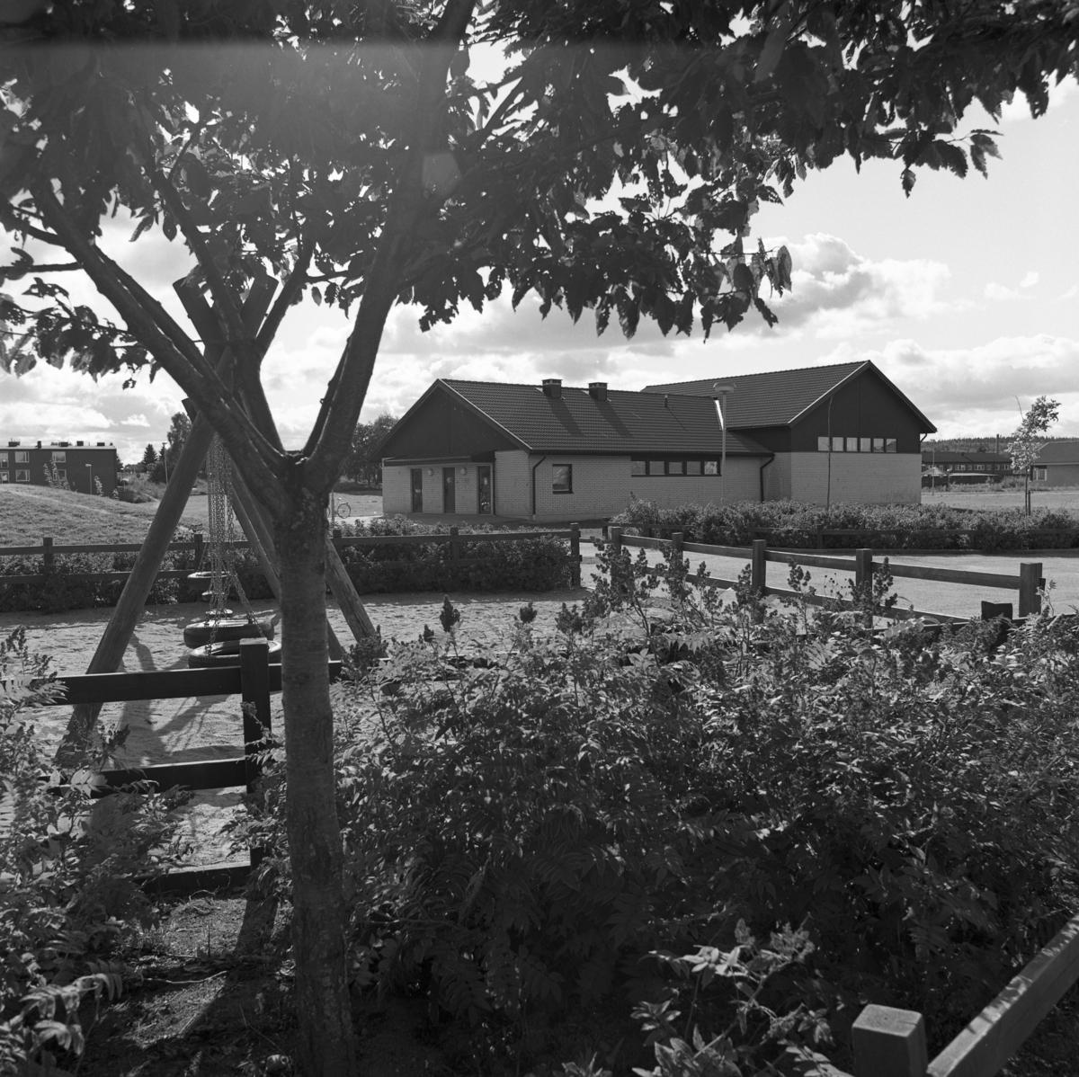 Ladubacksskolans gymnastiksal och gungor på skolgården. I bakgrunden ses flerfamiljshusen i kvarteret Sippan. Skolan byggdes 1982. Magnus Ledel, byggkonsult.
