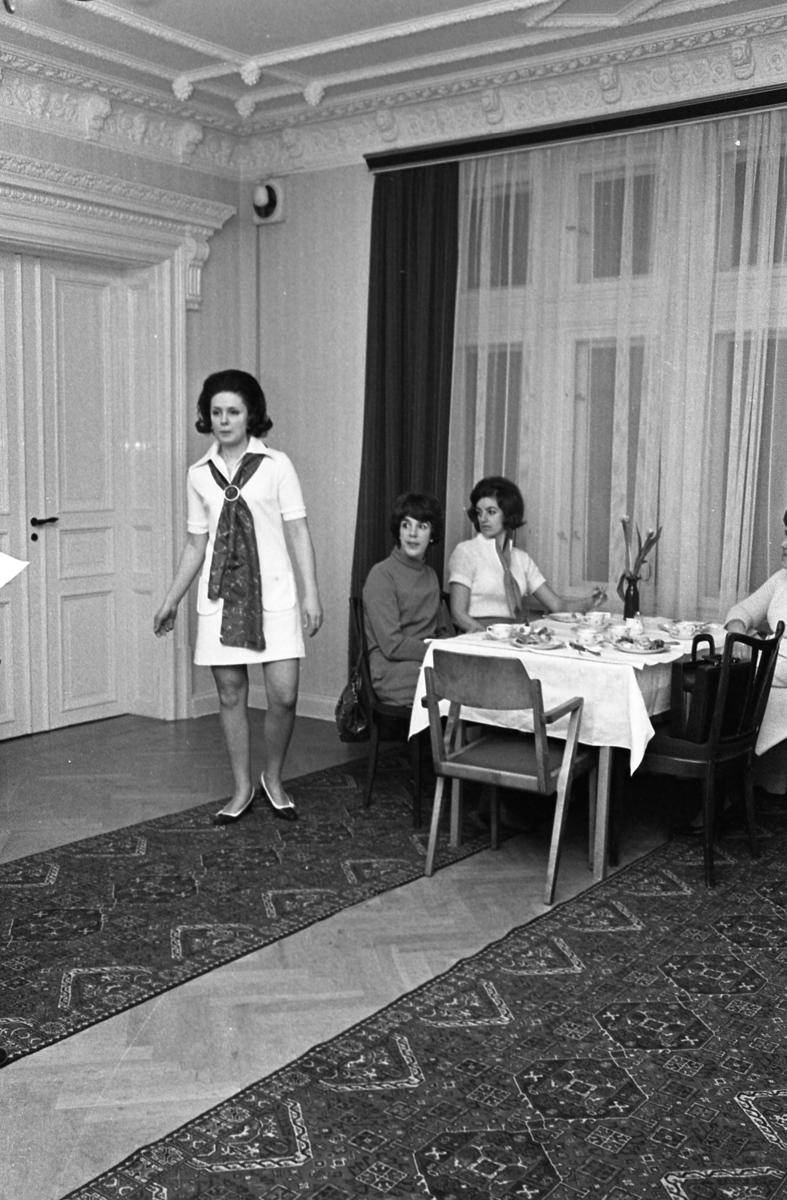 Modevisning ordnad av TBV, Tjänstemännens BildningsVerksamhet, som även bjuder på kaffe och landgång. Mannekängen visar en kort klänning med stor sjal. Vid bordet sitter Ingrid Östling och Anne-Marie Andersson. Eftersom Sture Melander ses på en bild i sammanhanget, kan man gissa att kläderna kommer från Öhrman & Melander.