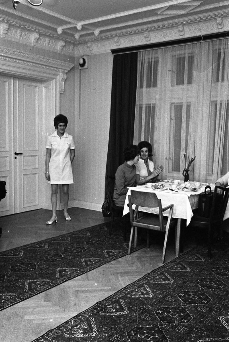 TBV, Tjänstemännens BildningsVerksamhet, ordnar mannekänguppvisning. Här visar Gunilla Magnusson en kort, ljus klänning. Vid kaffebordet sitter Ingrid Östling och Ann-Marie Andersson (närmast fönstret). Eftersom Sture Melander ses på en bild i sammanhanget, kan man gissa att kläderna kommer från Öhrman & Melander.