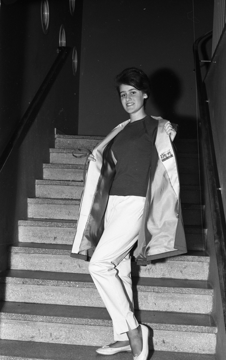 Öhrman & Melander har modevisning. Här är det Gunilla Strindler som visar upp sig för fotografen. Hon bär jumper och långbyxor med slits samt en lätt jacka. Bilden är tagen i en trappa.