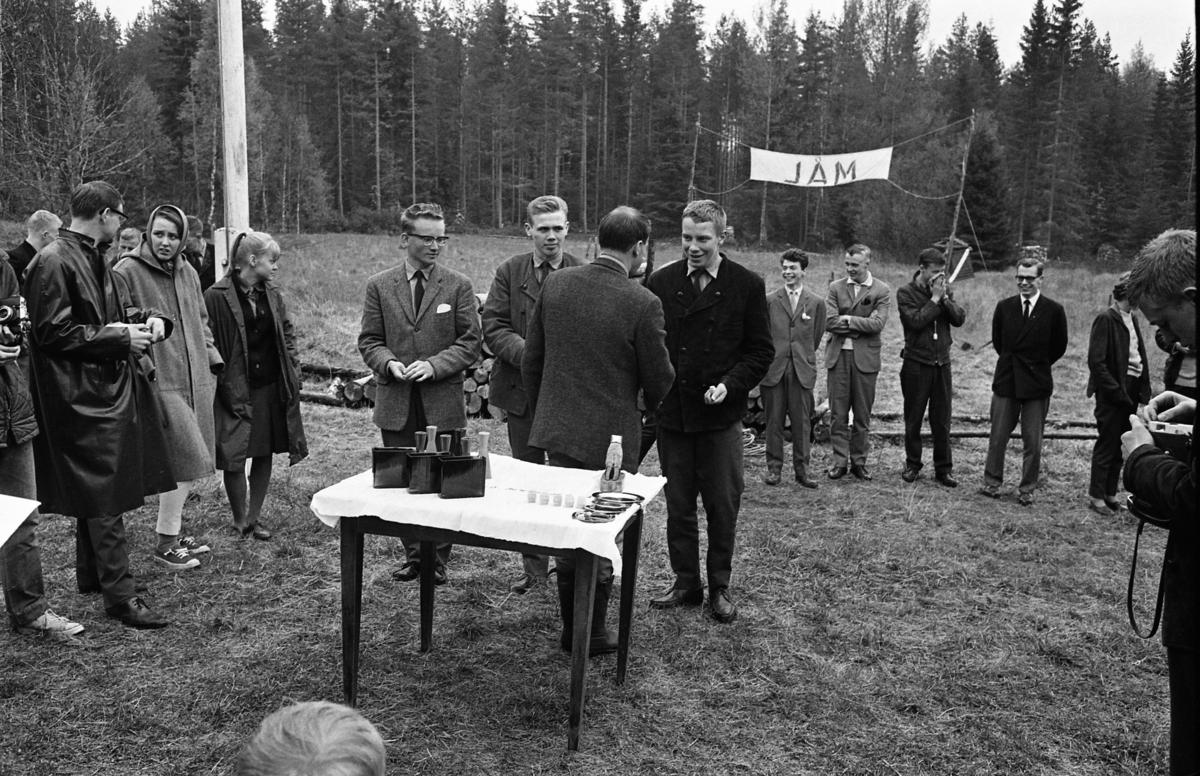 Scouternas budkavle-FM Prisutdelning utomhus. Prisbordet står dukat. Tre unga män gratuleras. Andra ungdomar står runt omkring och ser på. En man håller i en kamera. Platsen för målgången ses i bakgrunden.