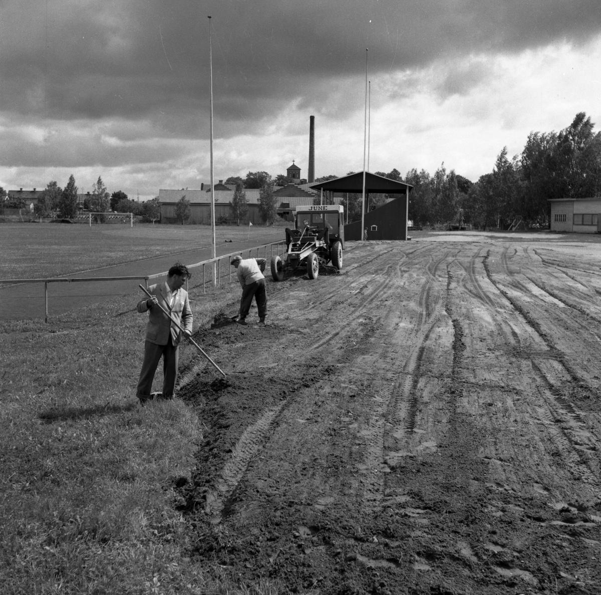 Sturevallen. Här förbereds för en ny ishockeybana. Två män och en traktor i arbete. Mannen i förgrunden är Olle Kropp. Bakom läktaren anas Arboga Margarinfabrik och tornet på Sankt Nikolai kyrka.