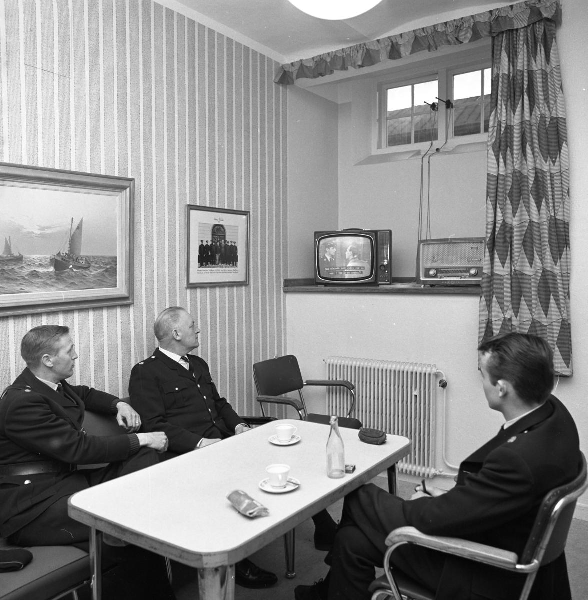 Nu finns det en TV-apparat i polisens dagrum! Tre uniformsklädda polismän sitter vid kaffebordet och ser en polisfilm på TV.  Från vänster: Bo Hammar, Gösta Brokvist och Jan Dovholt (med ryggen mot fotografen). TV´n står på fönsterbrädan. Där står även en radioapparat.