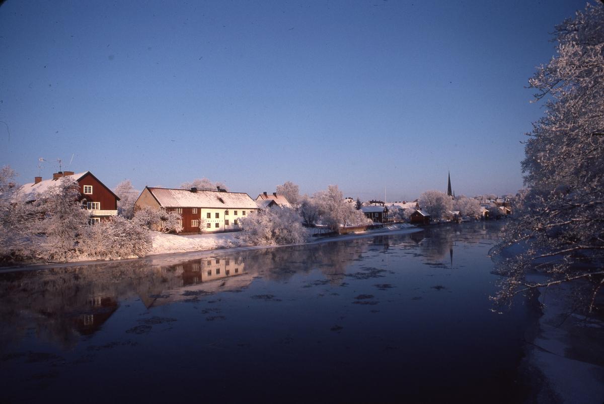 Vintervy över ågårdar längs Västerlånggatan. Det är snö. Spröda isskärvor i Arbogaån. Heliga Trefaldighetskyrkans torn till höger i bild. Bilden är tagen från Strömsnäsbron.