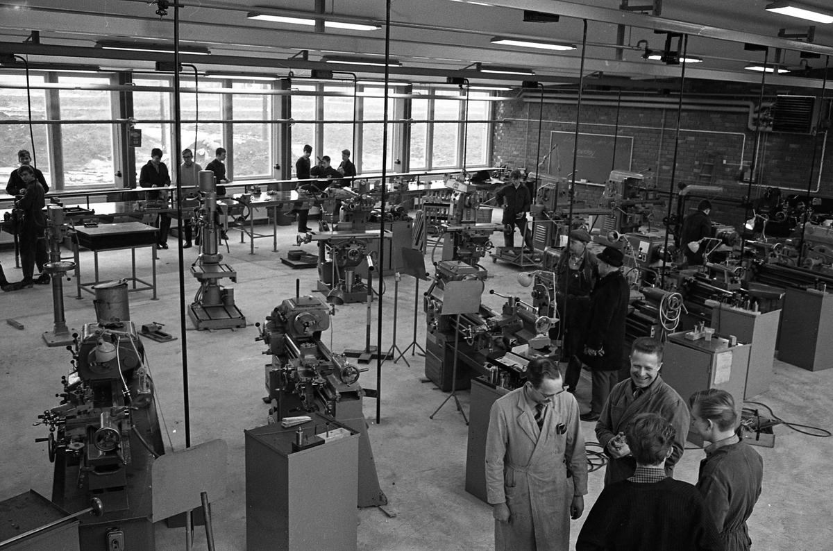 Yrkesskolan, maskinhallen. Elever vid maskiner. Två lärare, iklädda skyddsrockar, ses i bildens nedre högra hörn. Den vänstra, av dem, är yrkeslärare Otto Daunfelt. En man i hatt och ytterrock är på besök, mitt i bilden. Bilden ser ut att vara tagen i verkstaden på Vasagymnasiet.