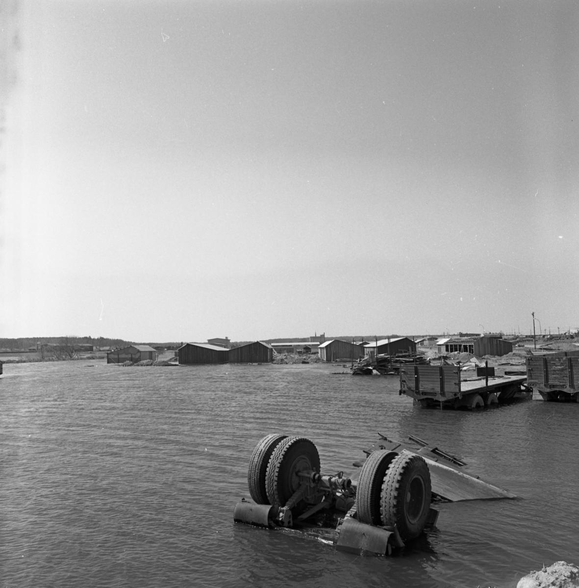 Arbogaån svämmar över. Norra Ågatan är drabbad av översvämning. Lastbilskärror står nedsänkta i vattnet, några hjul sticker upp över ytan. Längre bort, i bild, ligger några skjul omgivna av vatten.