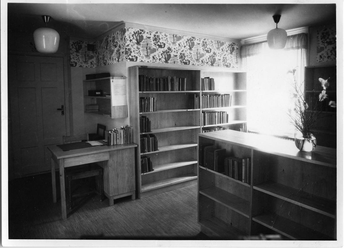 Biblioteket, interiör. Bokhyllor med böcker, ett skrivbord. Påskris i en vas. Troligen från biblioteket på Nygatan. Baksidan av detta fotografi kan ses på AKF-14450