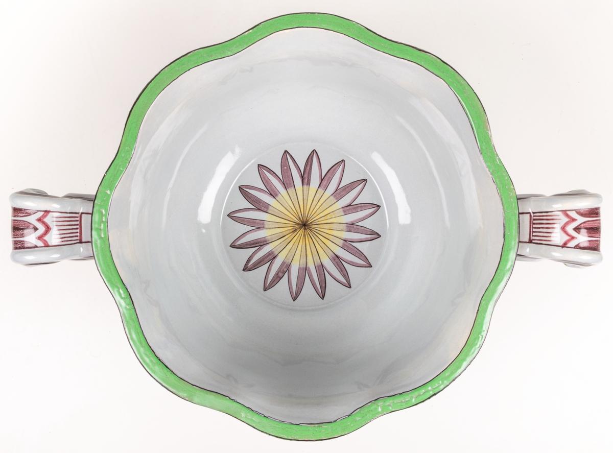 Vinbål med lock. Vit botten med målad dekor i svart, purpur, gul och grön färg. Locket dekorerad med skulpterad naken kvinna som ligger i en klase frukter. Skålens ena sida är dekorerad med en lyra, den andra med vinguden Bacchus sittandes på en tunna. Både skål och lock signerade Percy 1930.