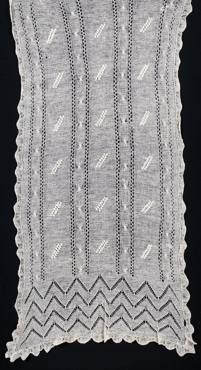 Axelschal av glest stickat yllegarn, benvit färg, istickade mönsterpartier.