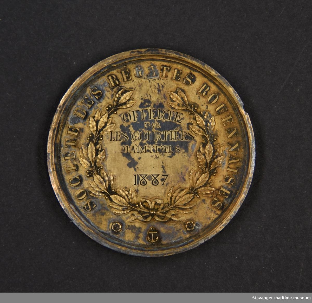 Medalje trolig av kobber med etui.  På den ene siden er det innskrifter, årstall og broderier, på den andre siden er det et regatta motiv.