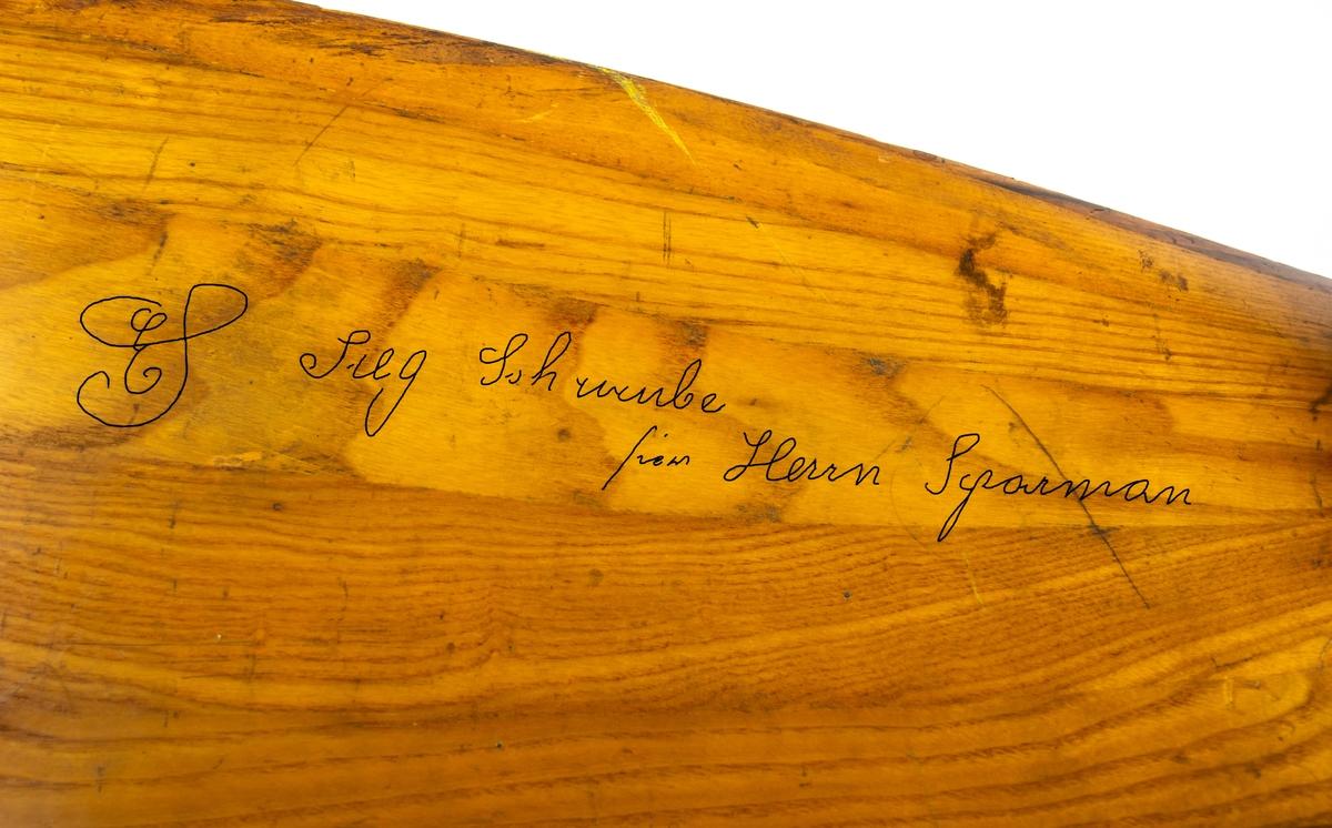 """Tvåbladig propeller i trä med gråmålat nav. Det finns åtta hål för att fästa navet. På bladen sitter ett märke med tillvärkarens logotyp: en tvåhövdad grip med texten Jacob Lohner & Co.  På baksidan av ena propellerbladet finns en svårtydd text skriven i blyerts, där det står bland annat """"Herrn Sparman""""."""