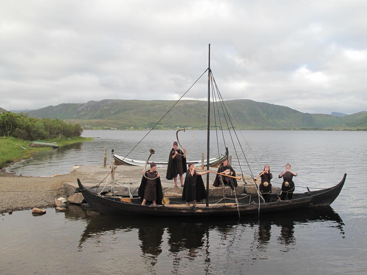 En liten seilbåt uten seil i masten ligger til land. Oppi båten står og sitter bronsealderkledde mennesker som spiller på lur.