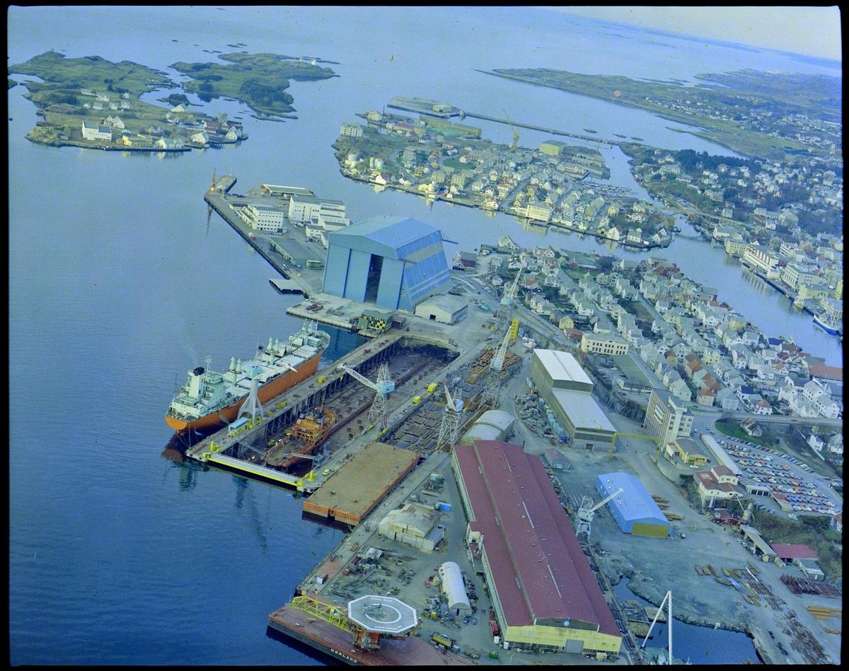 Flyfoto av Risøy med Haugesund Mekaniske Verksted i forgrunnen. Bak til venstre ligger Vibrandsøy, innenfor er Hasseløy og deretter kommer fastlandsdelen av Haugesund.