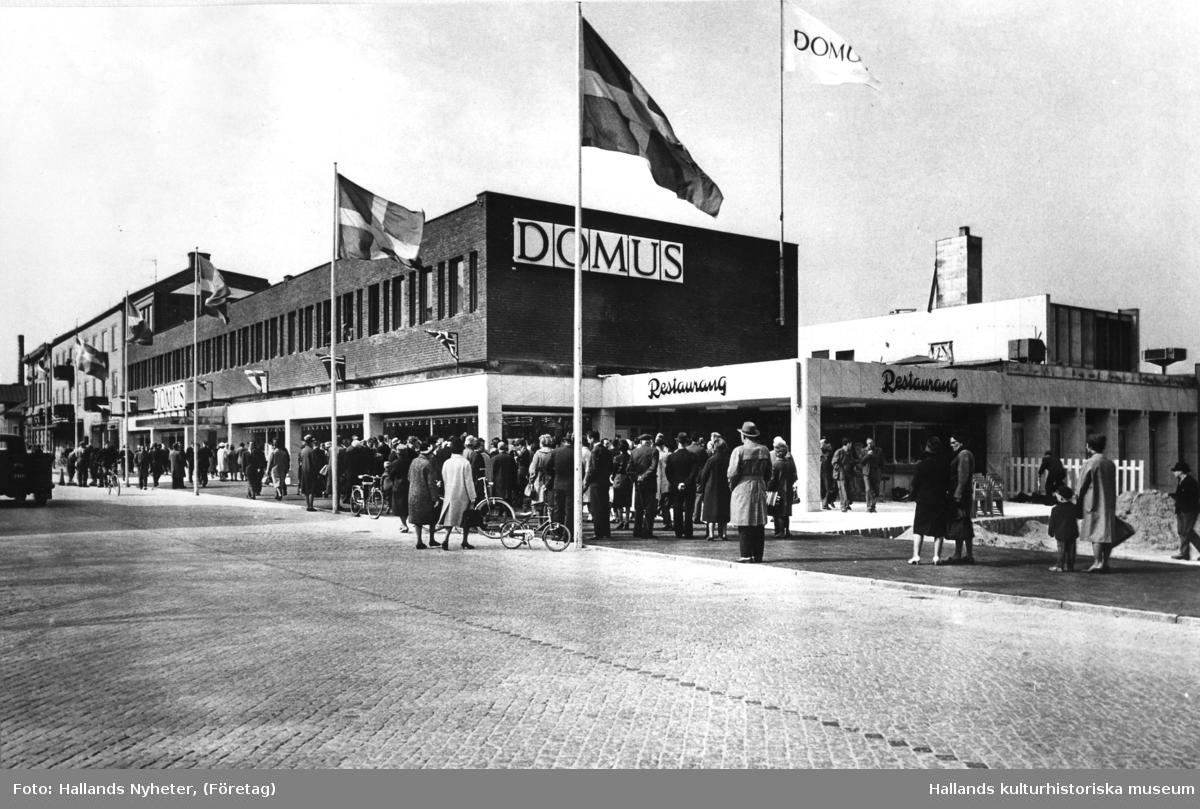 Hallands första fullt utbyggda Domusvaruhus invigs vid Västra Vallgatan i Varberg. Tillströmningen är så stor att polisen måste hjälpa till att ordna köerna. I förgrunden syns restaurangen. Arkitekt är Herman Borendal, KF:s arkitekt och ingenjörskontor.