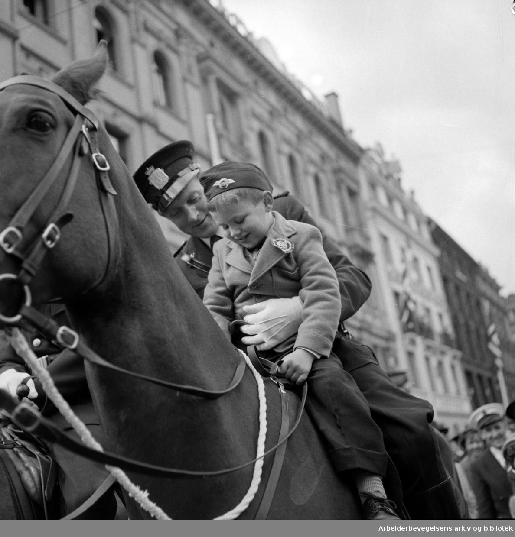 """17. mai 1956. """"Det var ikke alle som var så heldige som denne gutten som fikk sitte på politihesten hos en hyggelig konstabel.."""""""