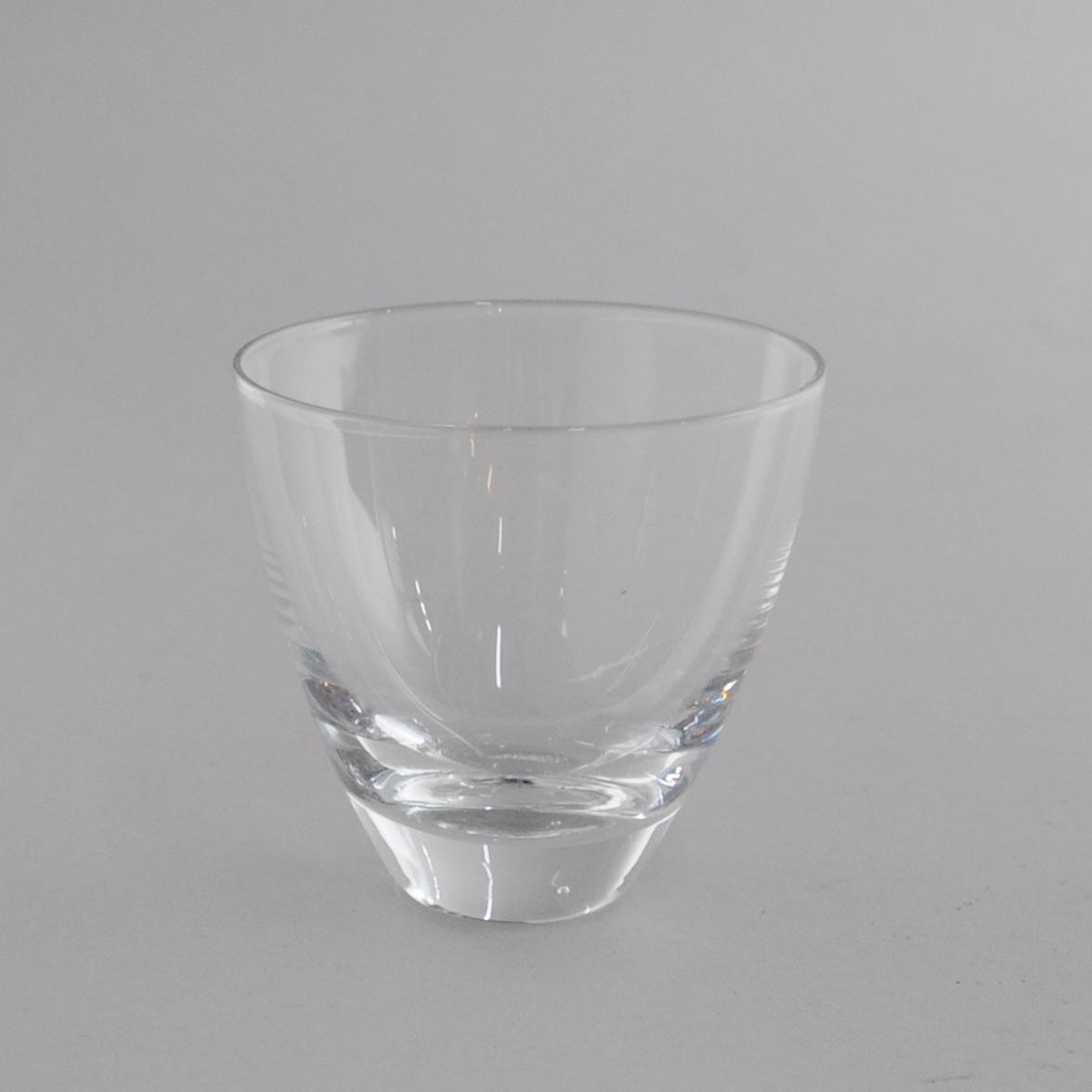 Glass til drikke. Glasset har utadgående kurvet form, med tykk bunn.