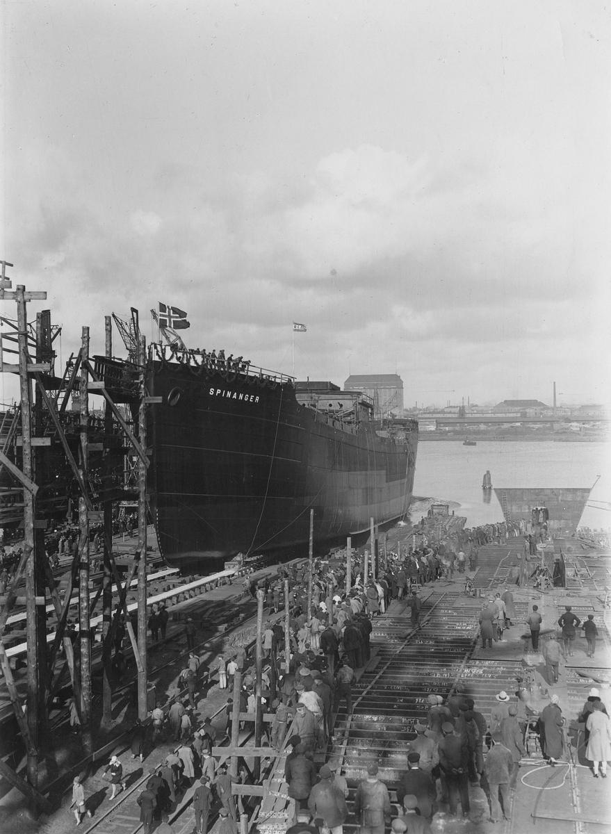 Motivet viser MT SPINANGER (bygget i 1927) under stabelavløpning ved Schieckau i Gdansk. Norsk flagg og rederiflagget til Westfal-Larsen. Verftsarbeidere og andre frammøtte i fremre del av motivet.