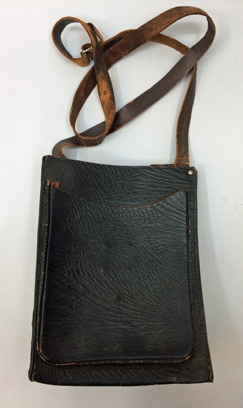 Väska av brunt präglat läder, med rem. Ett fack framtill, och flera mindre fack inuti.