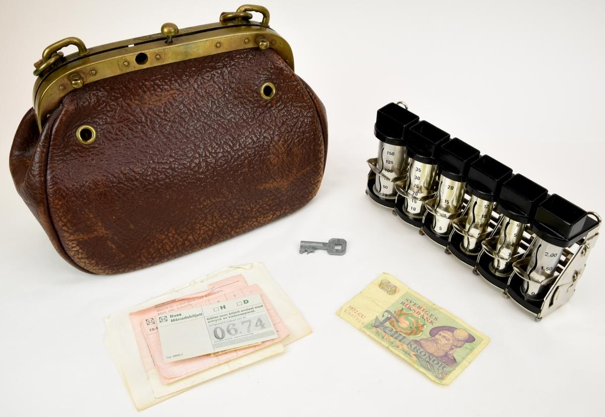 """Bussförarväska (:1) av mörkbrunt skinn innehållandes en mynthållare (:2) med mynt i. Bussförarväskan har ett bygellås av mässing. Myntbox av metall tillverkad av Sporrong. Väskan innehåller även en 5-kronorssedel (:3) samt en nyckel (Omärkt).  Mynthållaren har stativet, mekanismen och myntrören tillverkad av blank metall. Plast i """"mynttrattarna"""" och botten. Finns rör för myntvalörerna: 5 öre, 10 öre, 25 öre, 50 öre, 1 krona och 5 kronor. Mynt i rören: 5 öringar = 27 st 10 """" = 51 st 25 """" = 32 st 50 """" = 1 st 1 kr = 0 st 5 kr = 0 st  Alla mynt är omärkta.  Väskan innehåller även: 2 st fyrkantiga bussbiljetter i brunt papper med lila bläck som är något blekt. Den ena är från 6 maj 1974 och den andra från 20 maj 1974 (:4 :5). 1 st SJ buss månadsbiljett, grön text på vitt papper. Gällde juni månad 1974 (:6). 2 st SJ 10-biljett, oanvända. Grön text på rosa papper (:7 :8). 1 st del av check (till växelkassa?) (:9). 1 st kvittens till kassaapparat, grön text på vitt papper (:10)."""