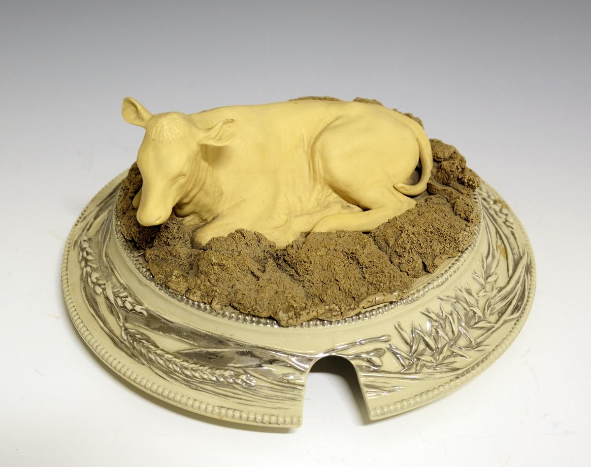 Stor punsjbolle i porselen med underfat og lokk. På lokket hviler en naturalistisk modellert kalv som ligger i gress eller halm. Fatet har en krans av modellert frukt rundt fanen. Selve bollen er stor og tung i formen, med fire modellerte, uglaserte dyrehoder, en okse, en ku, en hund og en hest. Mellom hvert av dyrene Jasperwarelignende ovale felter med ulike landbruksmotiver. Innimellom og rundt disse dekorelementene er sølvfarge modellerte blader med drueklaser imellom de øvrige dekorelementene.