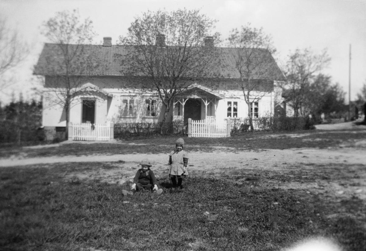 To barn i gresset med et våningshus i bakgrunnen