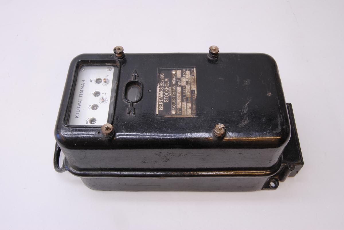 """3-fas kilowattimmätare. Instrumentet har ett hölje av svartmålat gjutjärn med två stycken glasfönster. Det finns ett hål upptill och två hål nedtill för montering med skruv. Upptill sitter ett handtag. Innanför glasfönstret sitter en tavla med fyra hål med siffror bakom som visar mätvärdet. Längst upp står det """"KILOWATTIMMAR"""". Från vänster ovanför hålen: 1000, 100, 10 och 1. Nedanför hålen sitter två små visare på varsin rund tavla med numren 0-9 numrerat motsols. Vid sidan om den vänstra står det 1/100 och vid sidan om den högra 1/10. På sidorna om glasfönstret sitter två skruvklämmor och ytterligare två  stycken sitter längre ned på instrumentets framsida. Nedanför glasfönstret sitter en mindre oval glasruta inramad av en pil i relief. Innanför glasrutan syns kanten av en metallskiva. Nedanför pilen sitter en tillverkarskylt med texten """"BERGMAN & BEVING STOCKHOLM IMPORT SOLAR-TREFAS-MÄTARE No. 371245 TYP. A1.T. 4 OLIKA BEL. FASER 4 LEDARE 5 AMP 190 VOLT 50 ~ 1 KILOWATTIMME = 1200 VARV."""" I instrumentets nederkant finns en låda med sju stycken utgångar för kablar."""