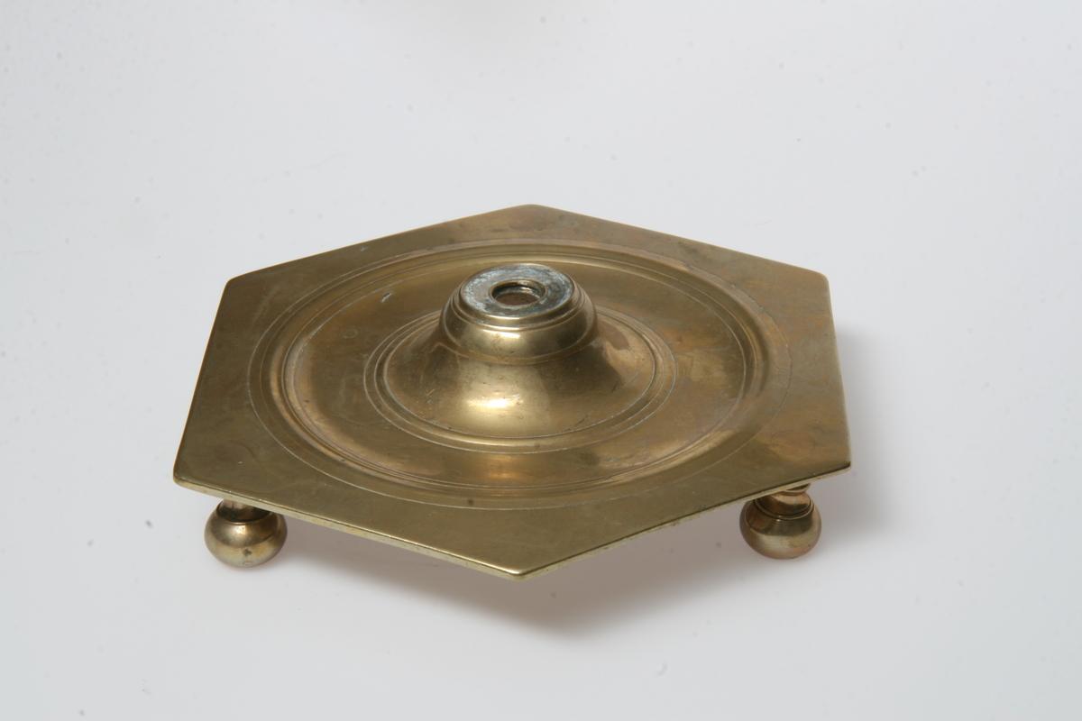 Balusterpipe (mangler) på sekskantet plate båret av tre kuler. Inngraverte ringer, noe mer på den ene. Lik som AS.310564.