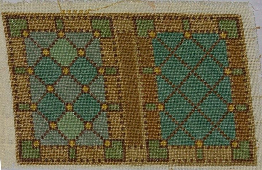 Ljusgul linnelärft, broderi, petit point. Beige botten med täckande mönster av romber, åttkanter, rektanglar m.m. i blå, gröna, gula och bruna nyanser, lingarn. Lärften har en stadkant.
