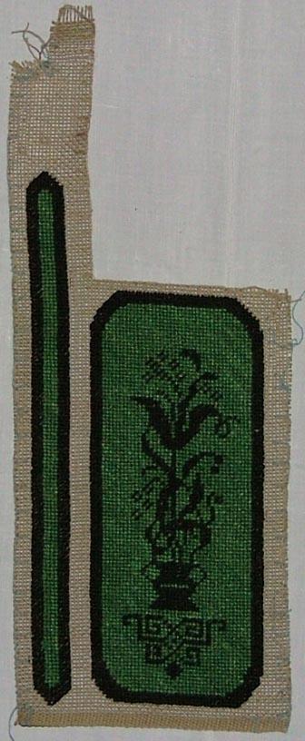 Beige, gles linnelärft, två broderier, petit point. Vänstra broderiet, långt och smalt, svart kant runt grönt mittparti, högra broderiet svart kant, svart blomranka på grön botten. Lärften har en stadkant, sydd med langettstygn.