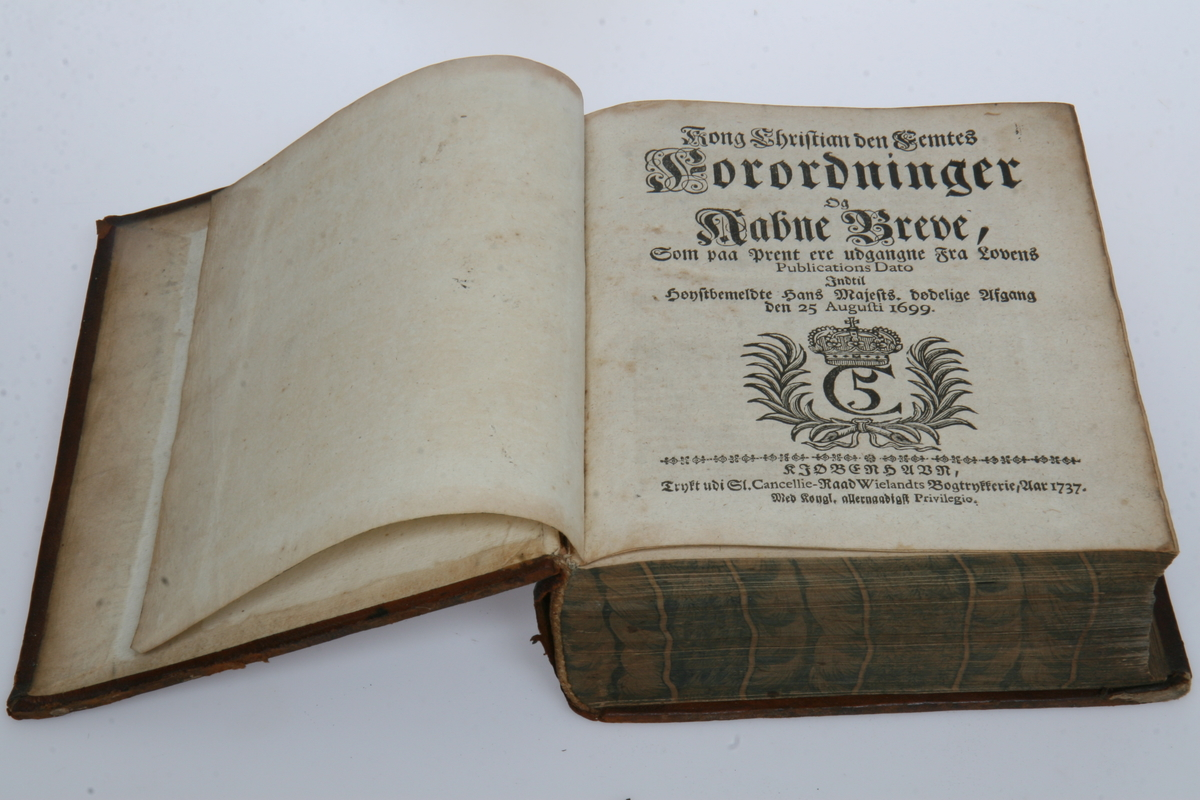 """Innbundet i skinn med gulltrykk. """"Kong Christian den Femtes Forordninger og Aabne Breve"""" (1683)-1699. København 1737."""