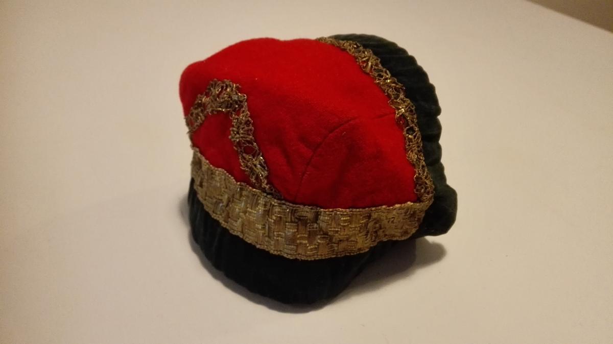 1 barnehue.  Av rødt vadmel, kantet med grønt fløiel og guldlisser, foret med stripet linlærred. Gave fra Ingebrigt Andersen Rislag, Vik.