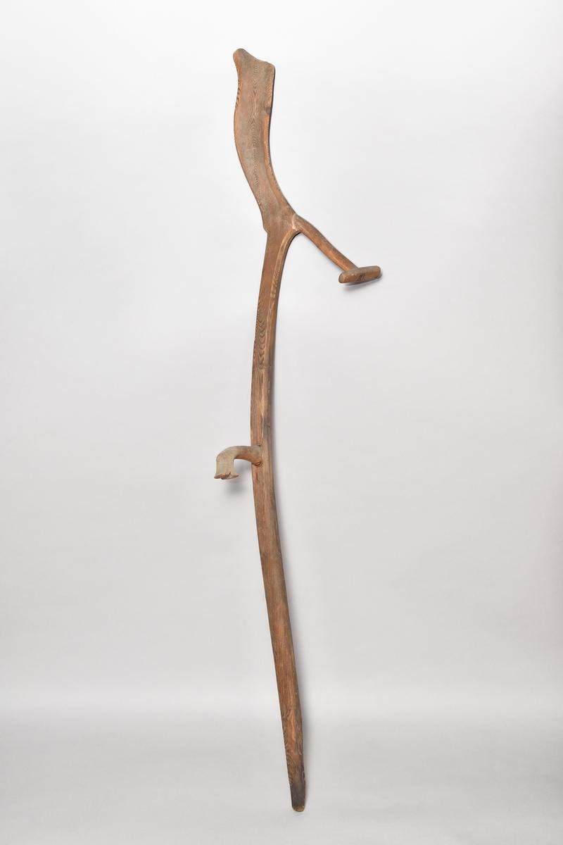 Lieorv av barrträ med handtag av björk. Bakre handtaget av självvuxen gren, handtaget på skaftet enkelt snidat, fågelliknande. Välvd ändplatta.
