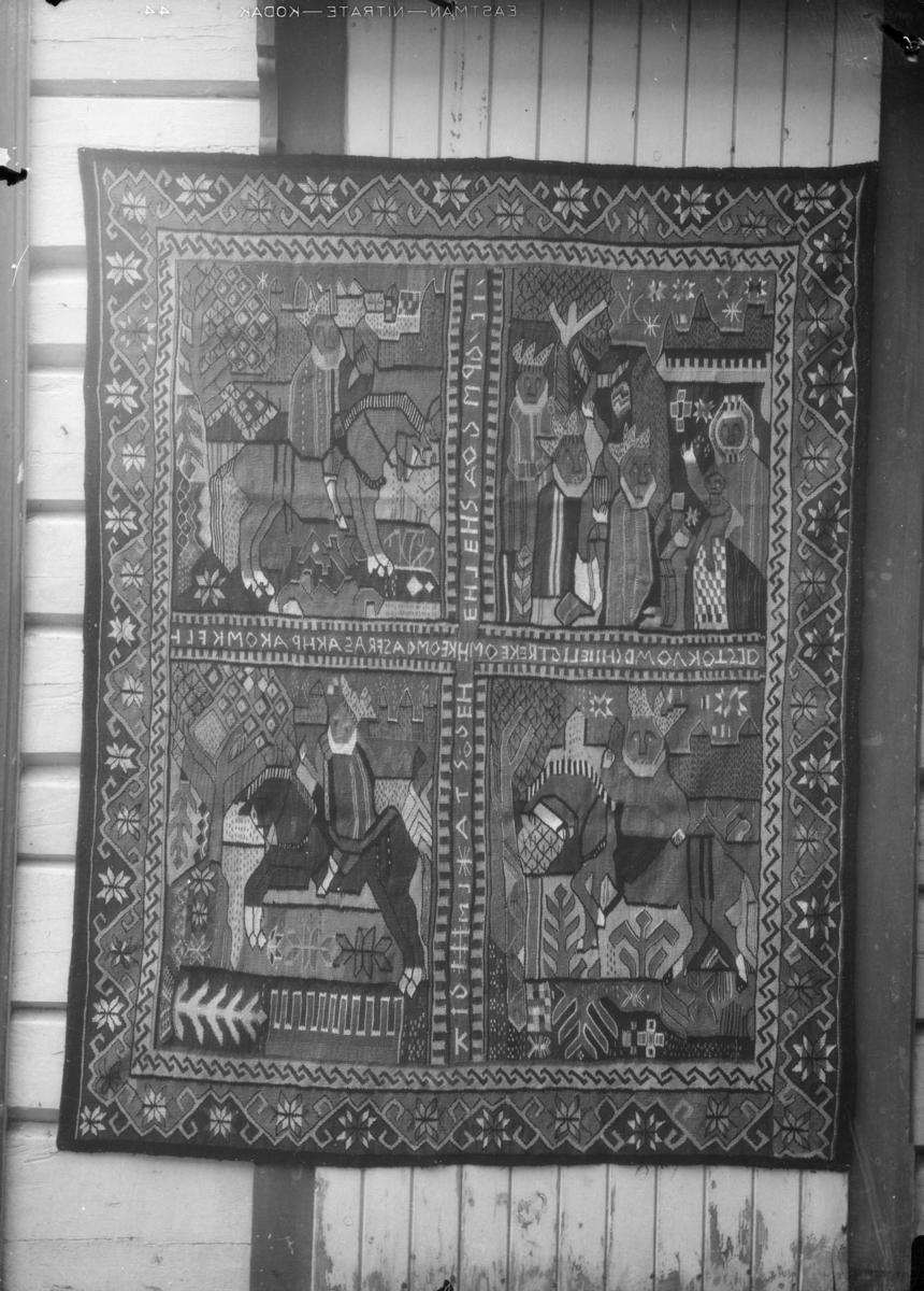 Billedvev, teppe med fire motivbilder av de Hellige tre konger. Skrift i kryss mellom bildene.