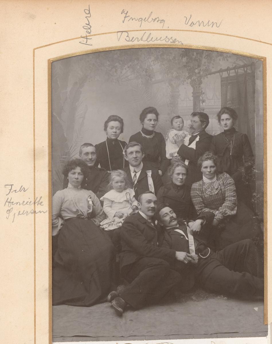 Studioportrett av 13 kvinner, barn og menn.