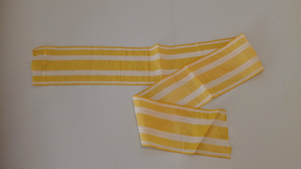 Rektangulær med langsgåande striper i kontrastfarge. Populært til småjenter i åra før og under verdskrigen 1914-1918 Karen Johanna, bestemor til gjevar, kan ha tenkt den til sine døtre.