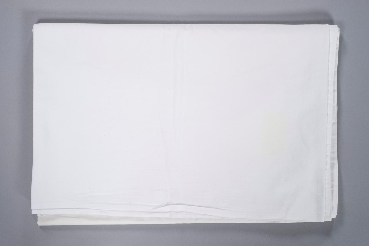 Hvitt rektangulært laken. Det er påsydd varemerke ved det ene hjørnet.