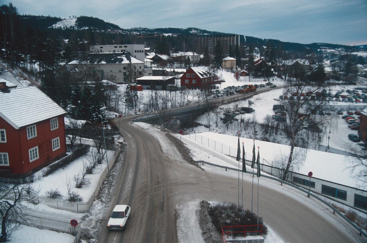 Lillehammer.  Spinnerivegen og Spinneribrua før ombygging til OL.  I forgrunnen til høyre atkomst til P-plassen ved Mesna-senteret.  I 2019 ble denne atkomsten fjernet i forbindelse med bygging av boligblokker.  Foto fra kran mot sør-øst.