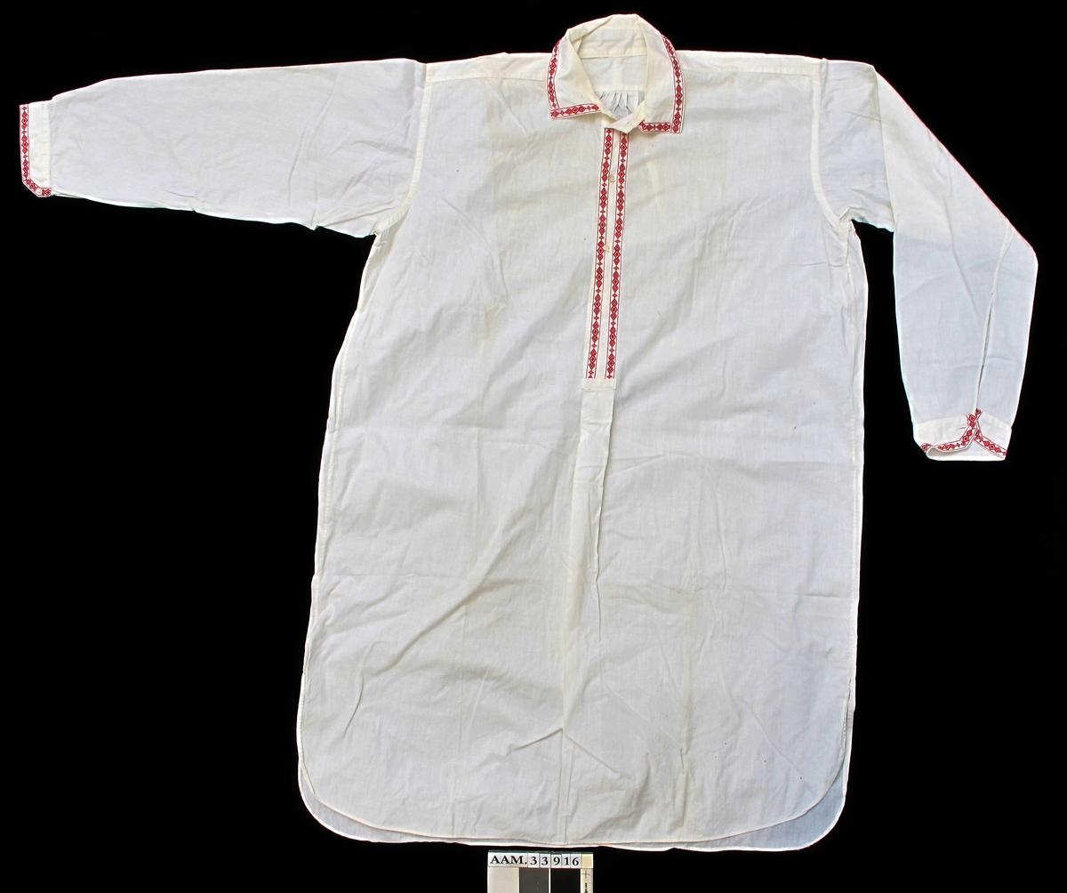 Lang skjorte, kort åpning i halsen, 3 små knapper. Tynt bomullstoff. Kantet åpninger med brodert bånd.