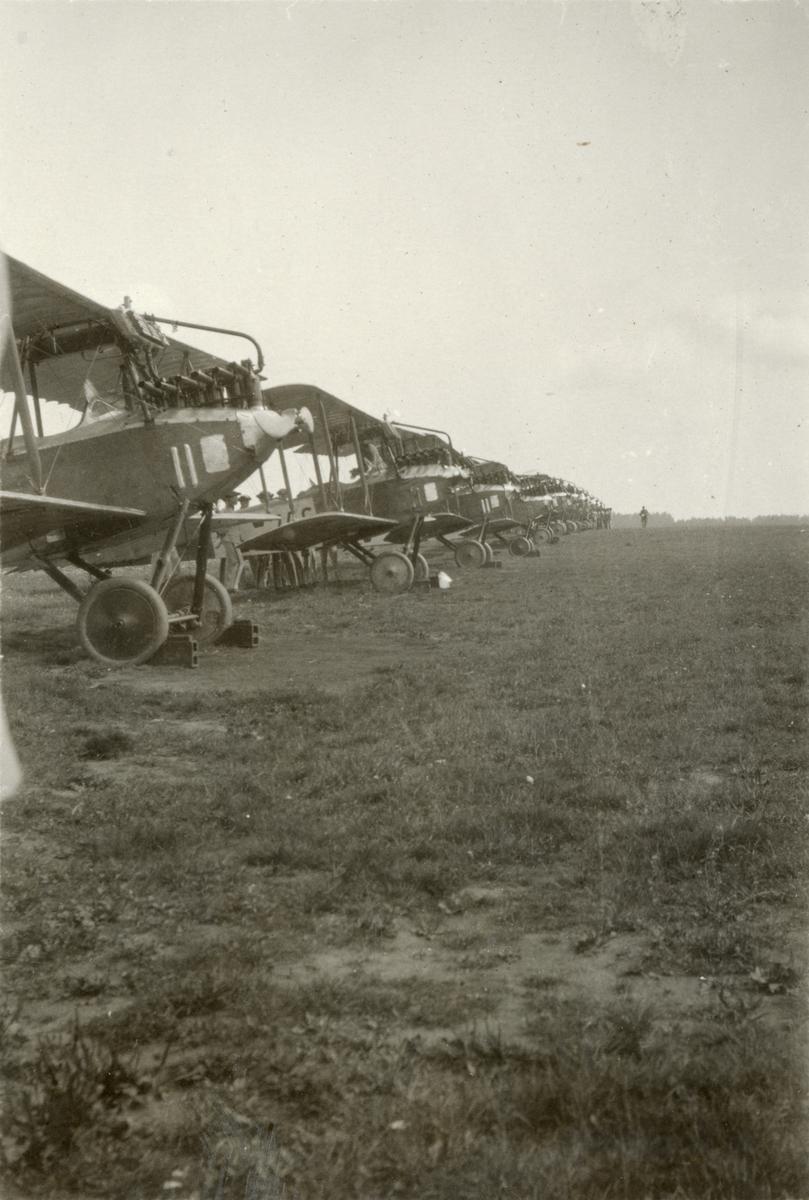 Flygplan uppställda i rad på flygfält.