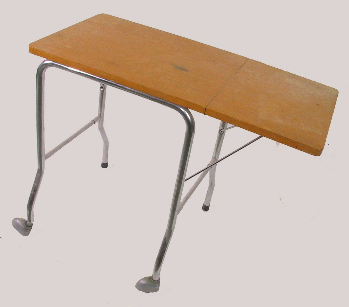 Lite bord av eikefinert plate og stålrørben. Med hengslet sideplate og hjul under to bein.