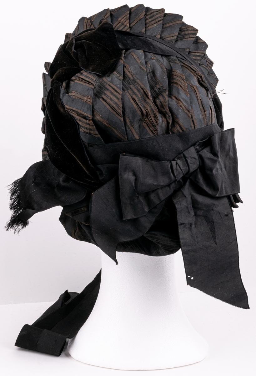 Damhatt, så kallad kapotthatt, svart/brun sidentyg med gula tygblommor.